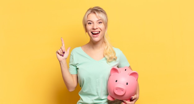 Blonde vrouw die zich als een blij en opgewonden genie voelt na het realiseren van een idee, vrolijk de vinger op te steken, eureka!