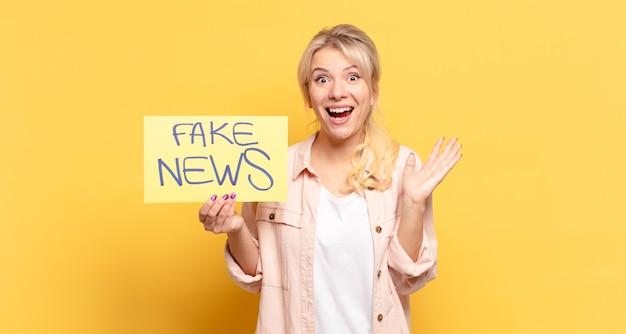 Blonde vrouw die zich blij, opgewonden, verrast of geschokt voelt, glimlacht en verbaasd is over iets ongelooflijks