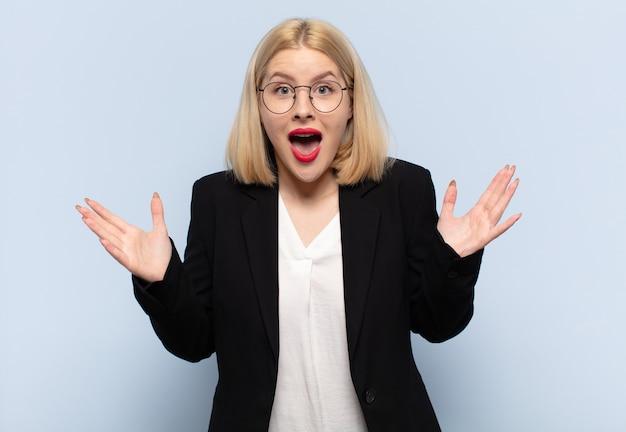Blonde vrouw die zich blij, opgewonden, verrast of geschokt voelt, lacht en verbaasd is over iets ongelooflijks