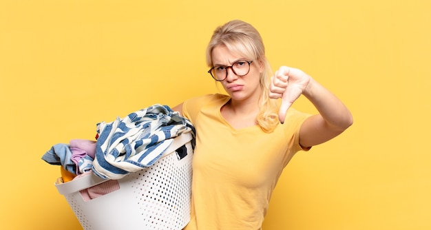 Blonde vrouw die zich boos, boos, geïrriteerd, teleurgesteld of ontevreden voelt, duimen naar beneden laat zien met een serieuze blik
