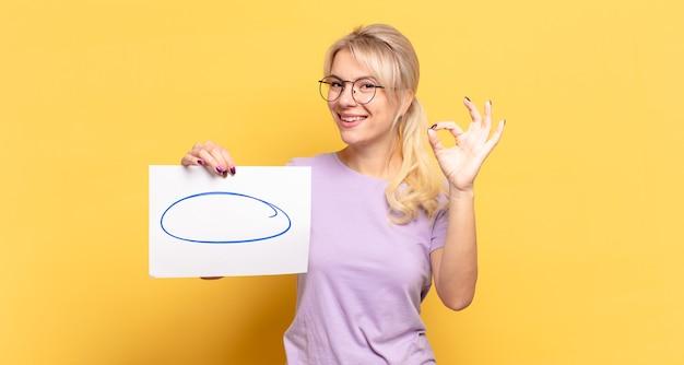 Blonde vrouw die zich gelukkig, ontspannen en tevreden voelt, goedkeuring toont met een goed gebaar, glimlachend