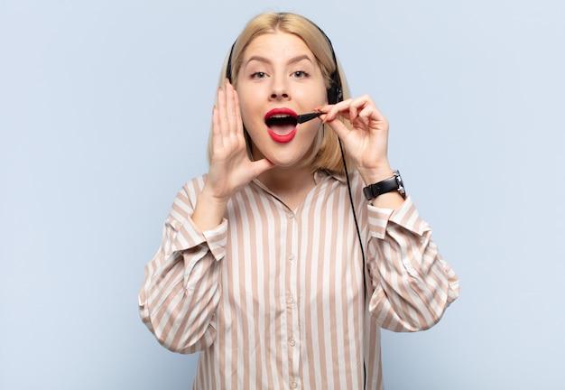 Blonde vrouw die zich gelukkig, opgewonden en positief voelt, een grote schreeuw geeft met de handen naast de mond, roept