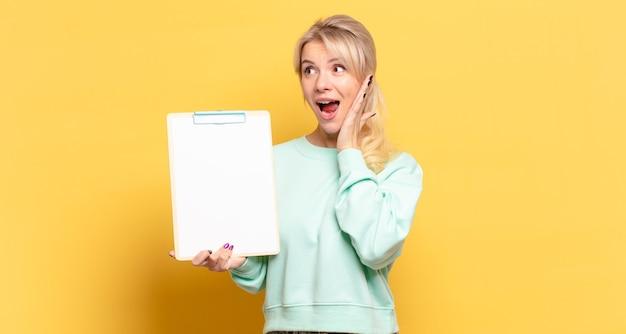 Blonde vrouw die zich gelukkig, opgewonden en verrast voelt, opzij kijkend met beide handen op het gezicht