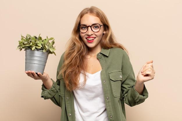 Blonde vrouw die zich geschokt, opgewonden en gelukkig voelt, lacht en succes viert, en zegt wow!