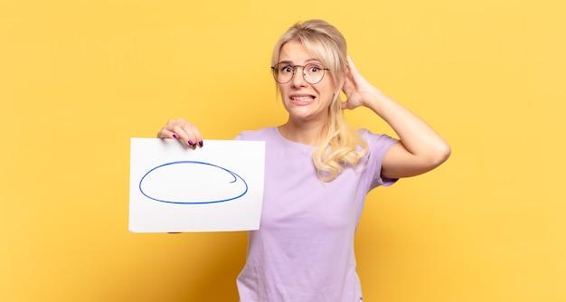 Blonde vrouw die zich gestrest, bezorgd, angstig of bang voelt, met de handen op het hoofd, in paniek bij vergissing