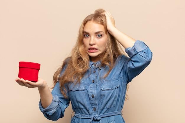 Blonde vrouw die zich gestrest, bezorgd, angstig of bang voelt, met de handen op het hoofd, in paniek raakt bij vergissing