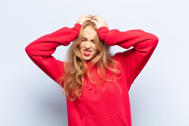 Blonde vrouw die zich gestrest en gefrustreerd voelt, haar handen naar haar hoofd heft, zich moe, ongelukkig en met migraine voelt
