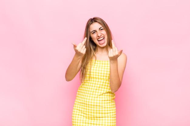Blonde vrouw die zich provocerend, agressief en obsceen voelt, de middelvinger omdraait, met een rebelse houding