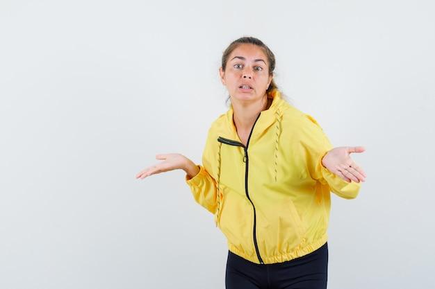 Blonde vrouw die zich uitstrekt handen op vragende wijze in gele bomberjack en zwarte broek en op zoek nieuwsgierig