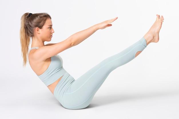 Blonde vrouw die zich uitstrekt in blauwe gym outfit