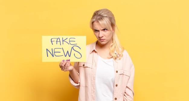 Blonde vrouw die zich verdrietig, boos of boos voelt en opzij kijkt met een negatieve houding, fronsend van onenigheid
