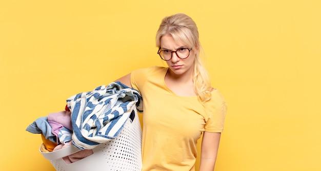 Blonde vrouw die zich verdrietig, boos of boos voelt en opzij kijkt met een negatieve houding, fronst van onenigheid