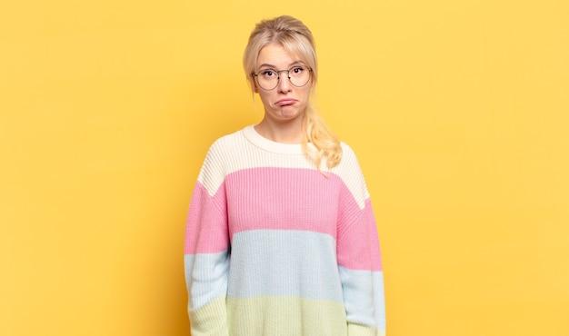 Blonde vrouw die zich verdrietig en gestrest voelt, van streek is vanwege een onaangename verrassing, met een negatieve, angstige blik