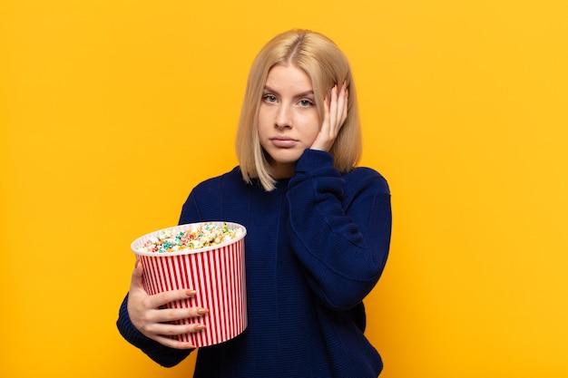 Blonde vrouw die zich verveeld, gefrustreerd en slaperig voelt na een vermoeiende, saaie en vervelende taak, gezicht met hand vasthoudend