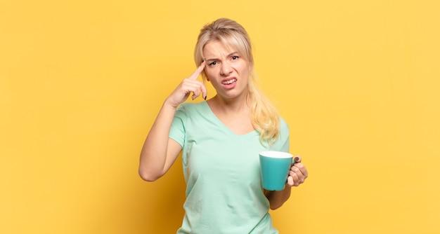 Blonde vrouw die zich verward en verbaasd voelt, laat zien dat je gek, gek of gek bent