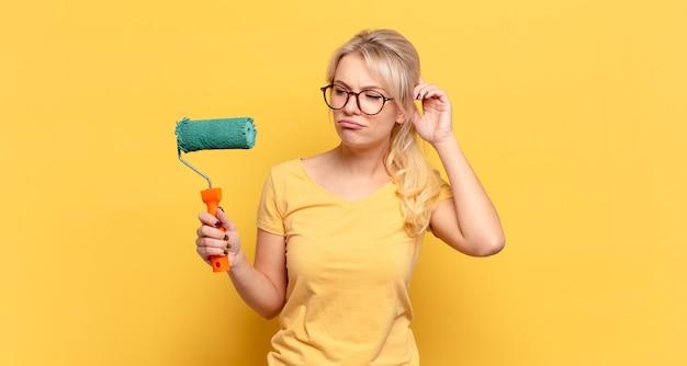 Blonde vrouw die zich verward en verward voelt, haar hoofd krabt en opzij kijkt