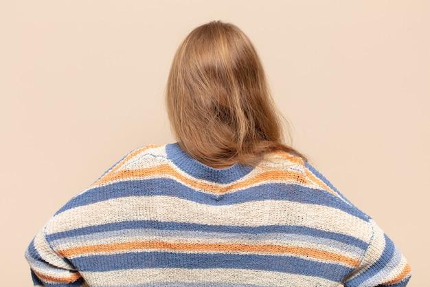 Blonde vrouw die zich verward of vol voelt of twijfels en vragen, zich afvragend, met de handen op de heupen, achteraanzicht