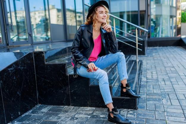 Blonde vrouw die zich voordeed op moderne straten. stijlvolle herfstoutfit, leren jas en gebreide trui. roze zonnebril.