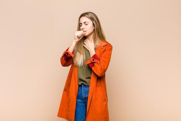 Blonde vrouw die zich ziek voelt met keelpijn en griepsymptomen, hoesten met bedekte mond