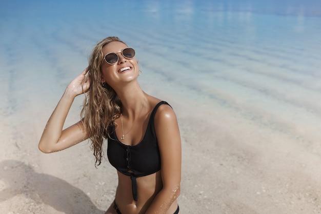 Blonde vrouw die zonnebril en bikini draagt die haar hoofd opheft en verrukt glimlacht.