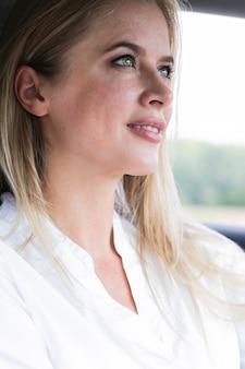 Blonde vrouw die zorgvuldig de weg bekijkt