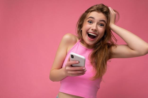 Blonde vrouw draagt roze top evenwicht geïsoleerd op roze achtergrond met lege ruimte in de hand houden en met behulp van mobiele telefoon communiceren online camera kijken.