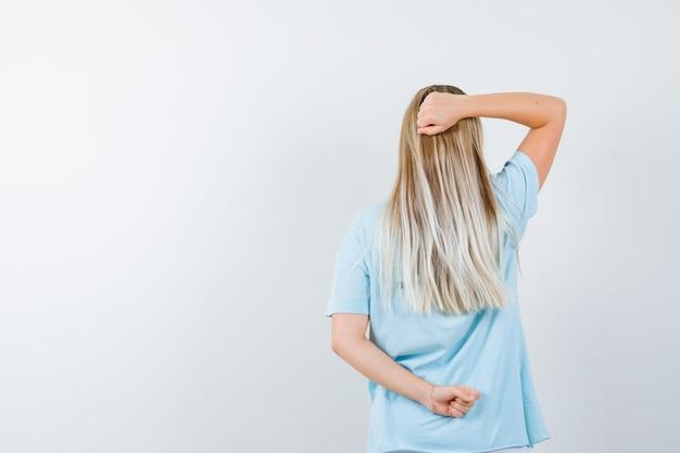 Blonde vrouw draait zich om, balt haar vuisten in een blauw t-shirt en ziet er schattig uit
