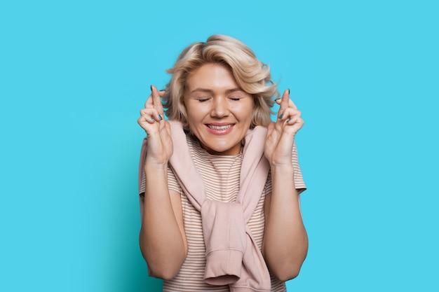 Blonde vrouw droomt over iets dat haar vingers kruist en poseert met gesloten ogen op een blauwe muur