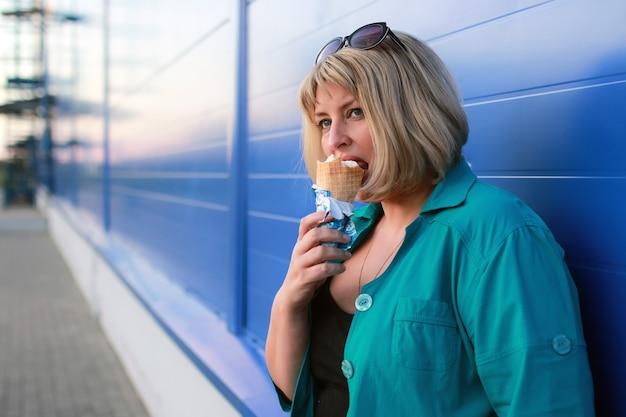 Blonde vrouw eet ijs buiten
