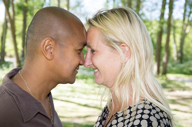 Blonde vrouw en een man van indiase afkomst maken een kus