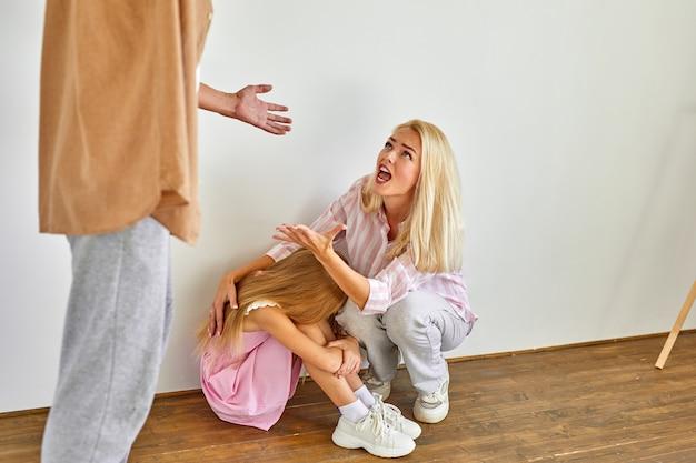 Blonde vrouw en kind meisje zit lijdt aan wreedheid van vader, beledigend relaties concept, man schreeuwt en straft familieleden