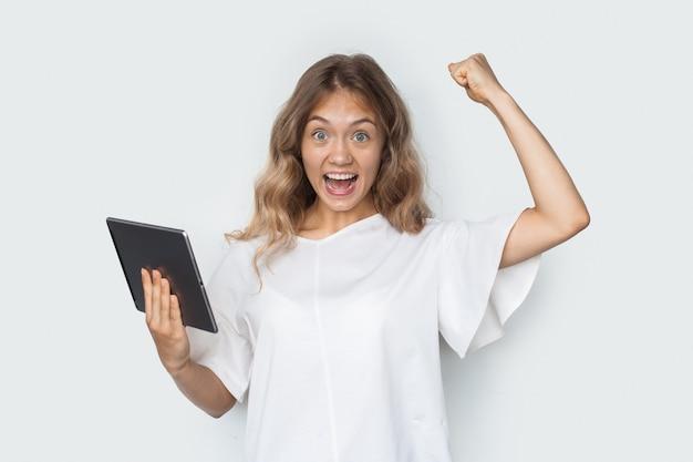 Blonde vrouw gebaart het ja-teken op een witte muur met een tablet en glimlacht naar de camera