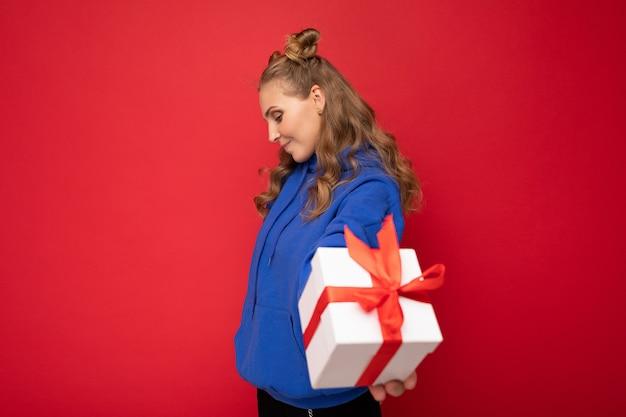 Blonde vrouw geïsoleerd op rode achtergrond muur draagt blauwe trendy hoodie met witte geschenkdoos met rood lint en op zoek naar de zijkant.