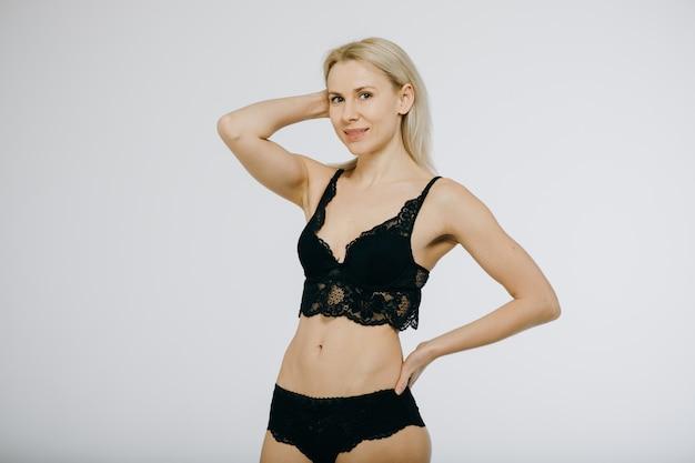 Blonde vrouw gelukkig glimlach poseren slijtage in zwarte lingerie, beha en slipje.