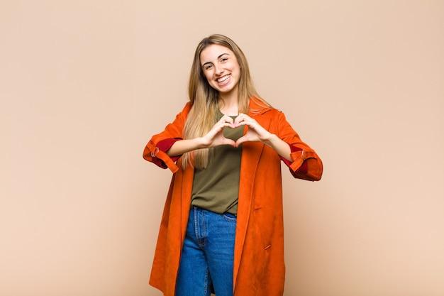 Blonde vrouw glimlacht en voelt zich gelukkig, schattig, romantisch en verliefd, hartvorm makend met beide handen