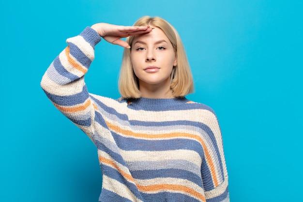 Blonde vrouw groet de camera met een militaire groet in een daad van eer en patriottisme en toont respect