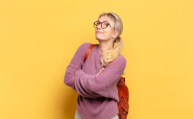 Blonde vrouw haalt haar schouders op, voelt zich verward en onzeker, twijfelt met gekruiste armen en kijkt verbaasd