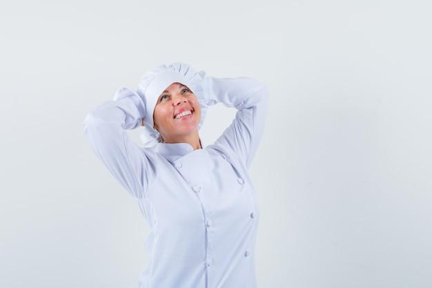 Blonde vrouw hand in hand achter het hoofd, na te denken over iets in witte kok uniform en ziet er mooi uit.