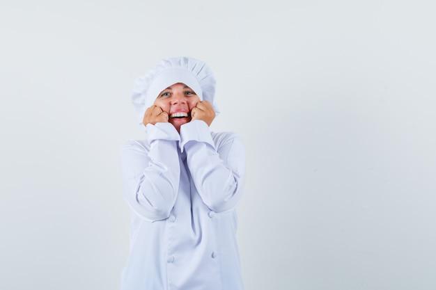 Blonde vrouw hand in hand op kin, balde vuisten in witte uniform koken en er mooi uit.