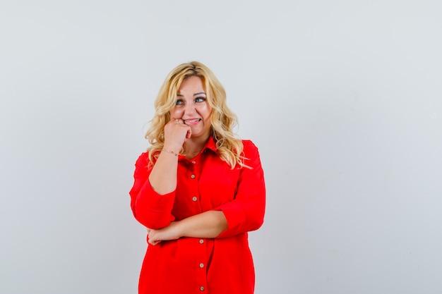 Blonde vrouw hand op de wang zetten, staande in denken pose in rode blouse en peinzend kijken. vooraanzicht.