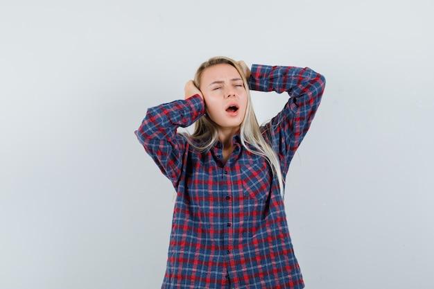 Blonde vrouw handen op de oren te drukken, permanent met open mond in geruit overhemd en uitgeput, vooraanzicht op zoek.