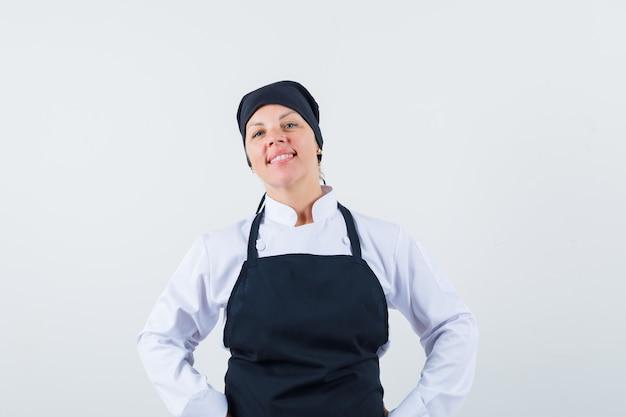 Blonde vrouw handen op taille, die zich voordeed op camera in zwarte uniform koken en er mooi uitzien. vooraanzicht.