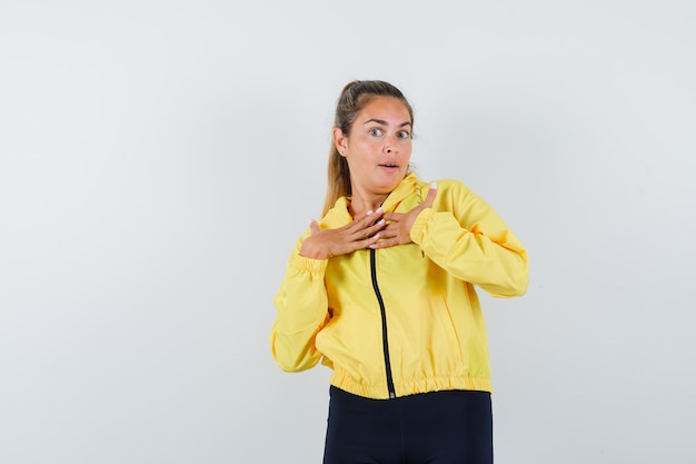 Blonde vrouw handen rusten op de borst in geel bomberjack en zwarte broek en verbaasd kijken