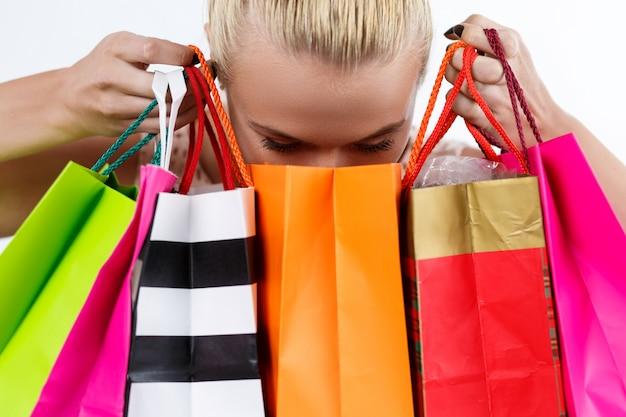 Blonde vrouw het inspecteren inhoud van gekleurde document zakken met het verse kopen