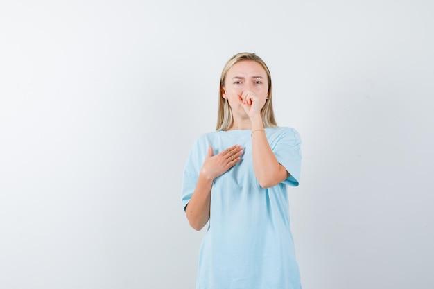 Blonde vrouw hoest, houdt vuist op mond in blauw t-shirt en ziet er uitgeput uit