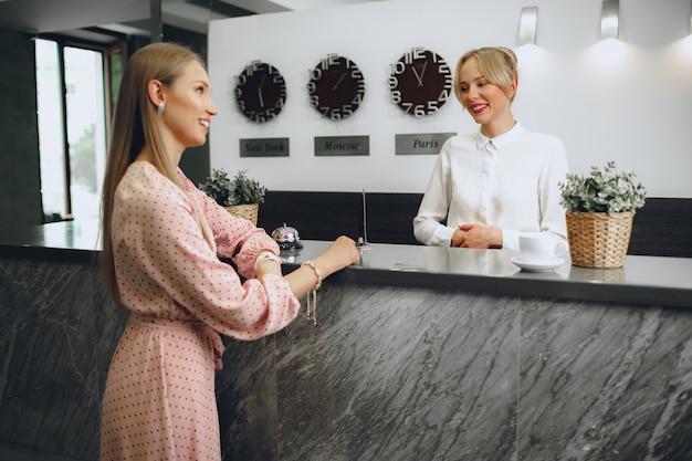 Blonde vrouw hotelgast inchecken bij receptie in hotel