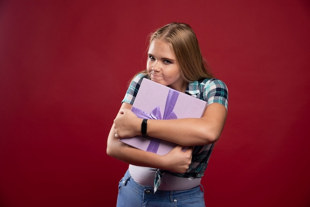 Blonde vrouw houdt een geschenkdoos stevig vast en wordt jaloers als ze het deelt.