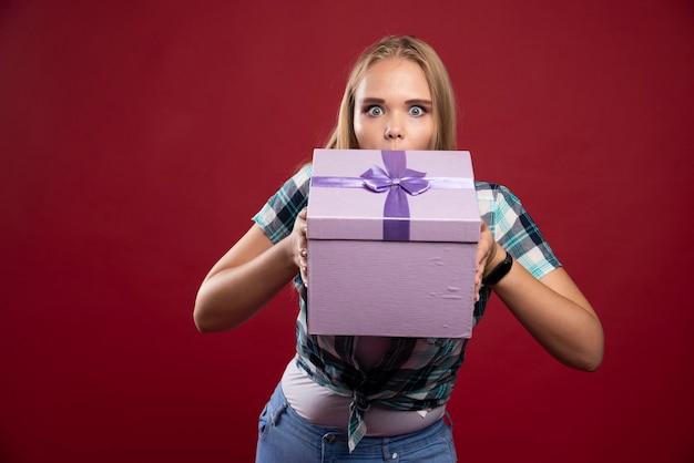 Blonde vrouw houdt een geschenkdoos stevig vast en ziet er verward en ontevreden uit.
