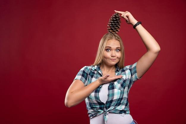 Blonde vrouw houdt eikenboomkegel aan haar hoofd en voelt zich positief.