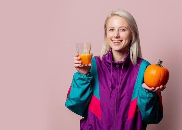 Blonde vrouw in 90s trainingspak met pompoensap in glas op roze